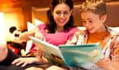 In the comfort of the Disneyland Hotel room, a boy reads a Disney storybook to his mom.