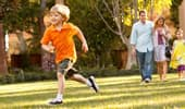 A young boy runs on the grass while his family looks on.