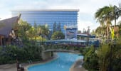 A wide shot of the Disneyland Hotel, one of the 3 pools and the footbridge.