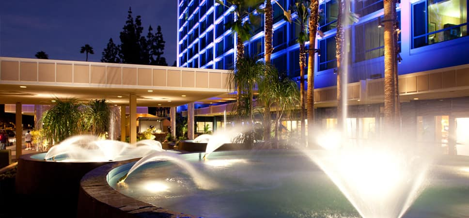 A nighttime shot of the Fantasy Tower fountains at the Disneyland Hotel entrance.