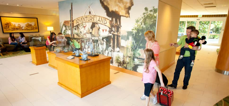 Guests look at character maquettes and statues in glass cases on display in the lobby.