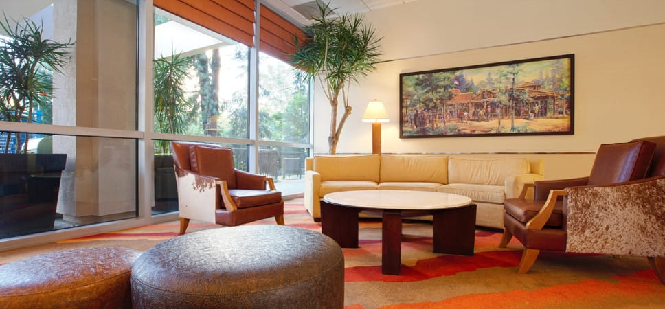 The lobby's waiting area is decorated with wood, leather and warm earth tones.