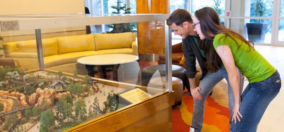 A couple looks into a large glass case that contains a replica of part of the Disneyland Theme Park in miniature.
