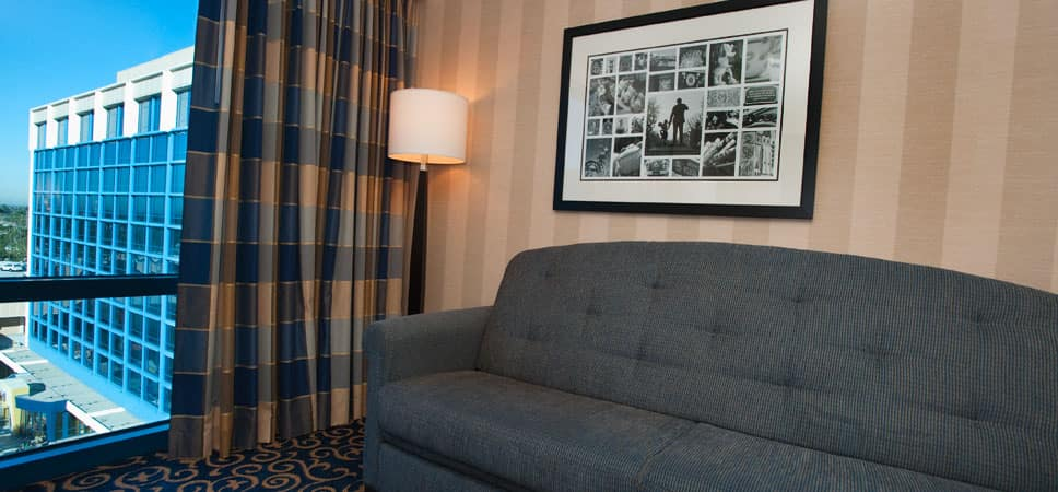 A comfortable sofa sits beneath a framed collage of images from Disneyland history.