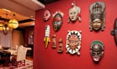 Masks decorate an intensely red wall.