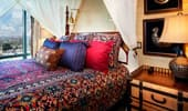 Bed with brightly colored pillows and spread.