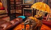 Lámpara artística y caprichosa: un mono monta un elefante sosteniendo una sombrilla que también es la pantalla de la lámpara.