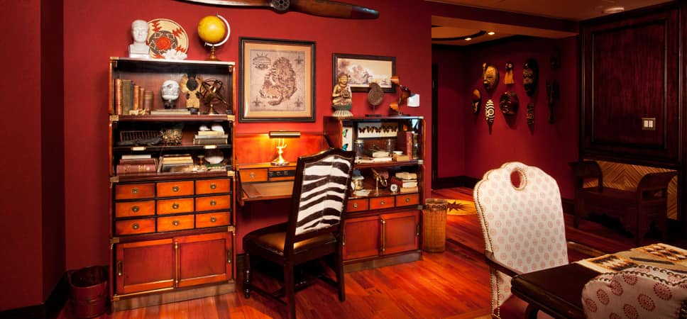Writing desk, surrounded by maps, globes and curios.