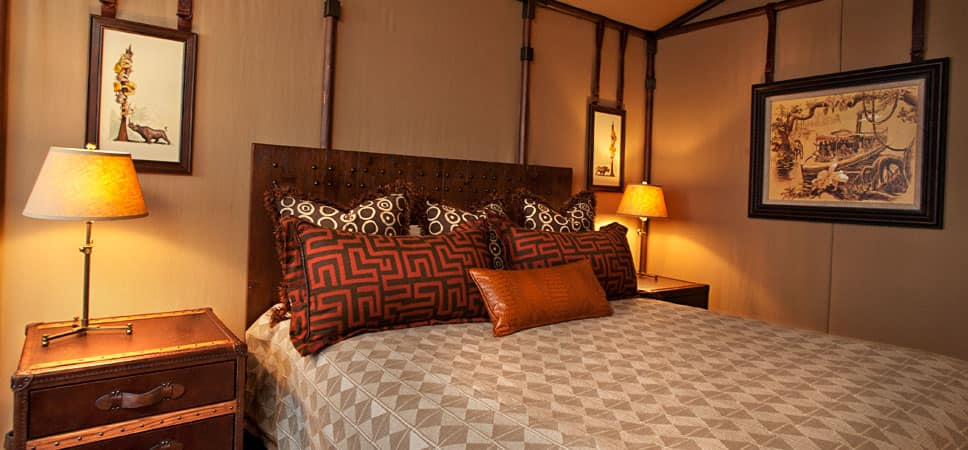 Large bed, surrounded by steamer trunk tables and Adventureland artwork.