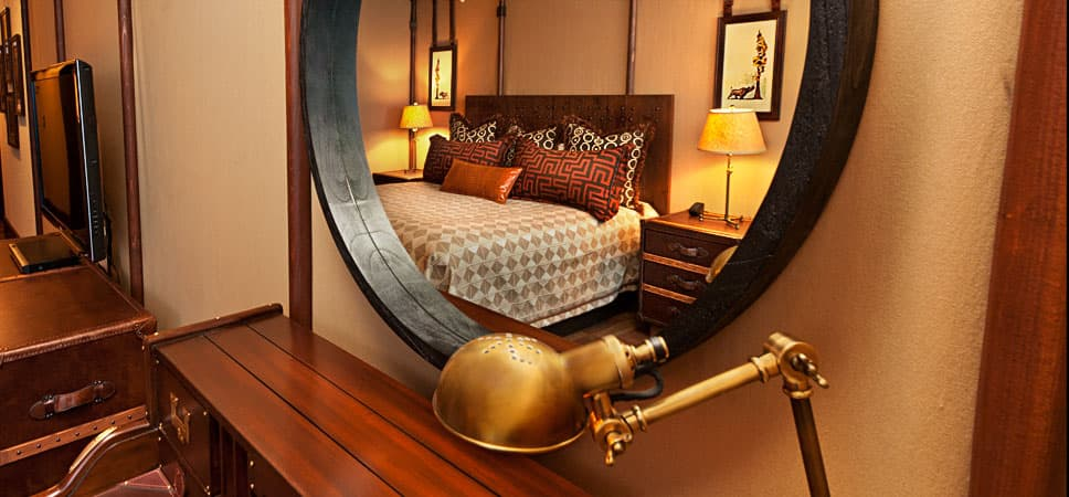 Reflection of bed and surroundings framed in a mirror.