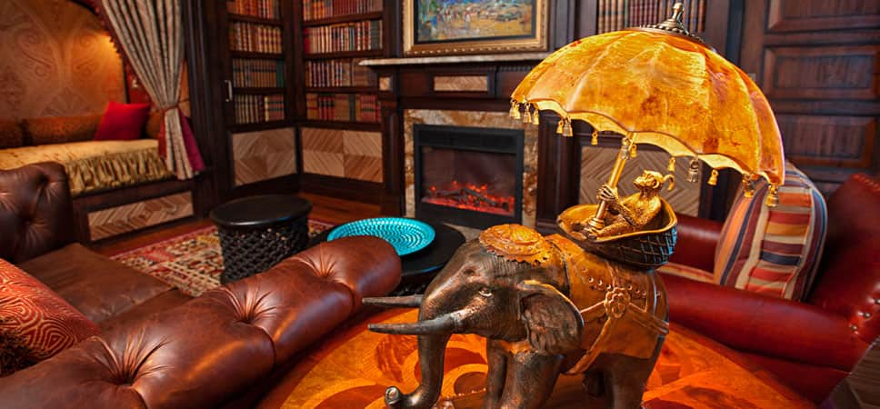 An artistic and whimsical lamp: a monkey riding an elephant, holding an umbrella that doubles as the lamp shade.