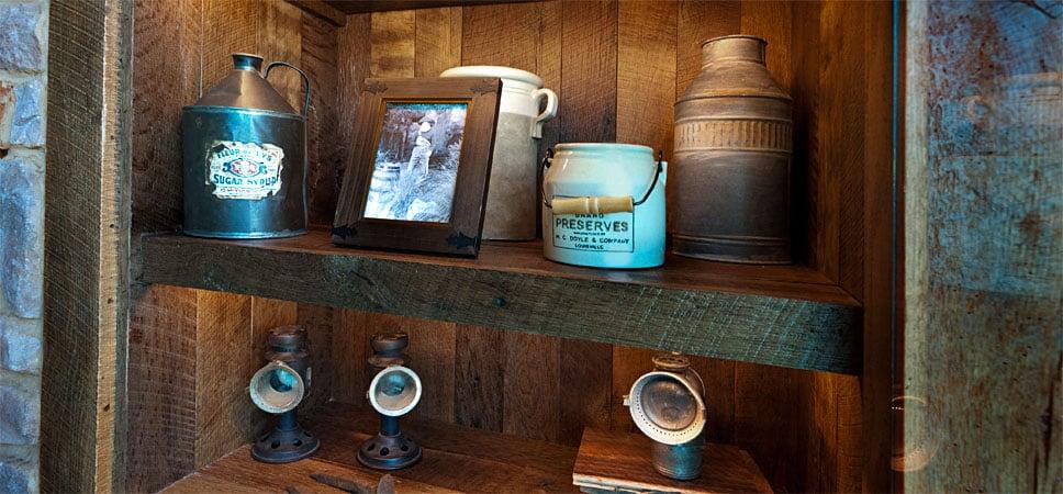 Frasco de conservas, lata de miel, jarros y fotos enmarcadas.