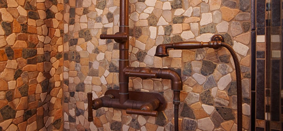 Shower fixtures surrounded by stone work.