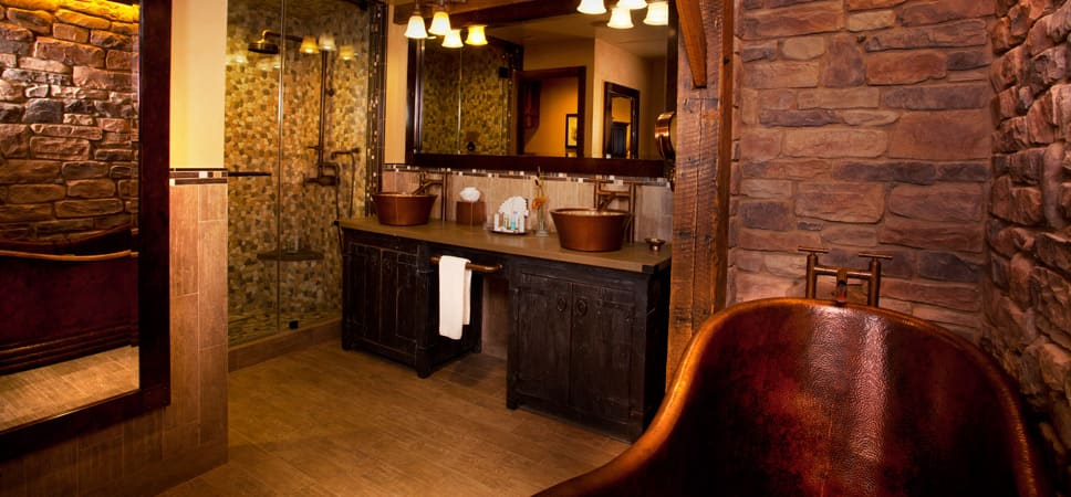 Wide shot of the wash room with 2 sinks, copper-finished tub and shower stall.