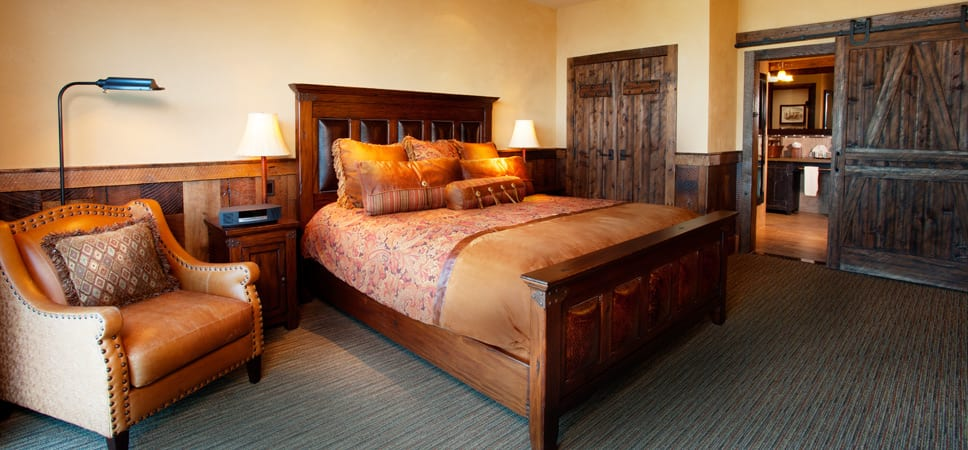 King bed in a room designed with wood and leather.