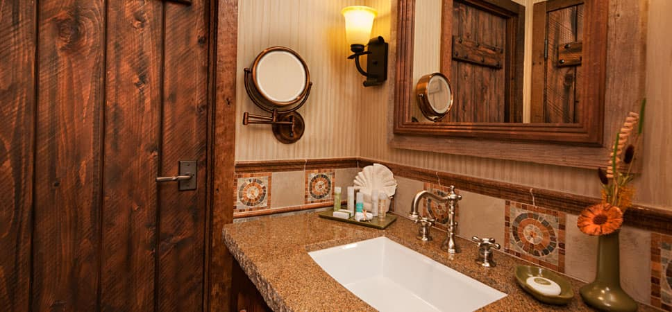 A marble sink, mirrors and wood door.