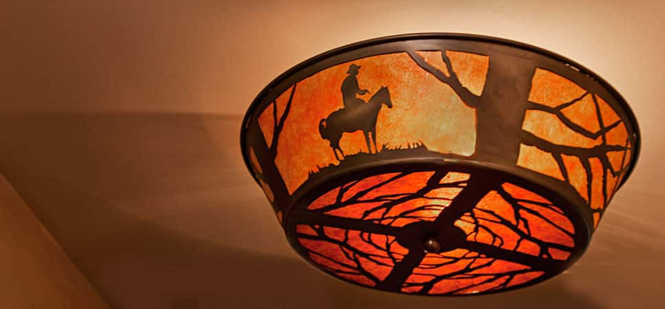 Overhead light fixture with silhouettes of tree branches and a miner on a horse.