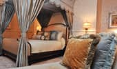 A canopied king bed, an elegant couch and plush pillows.