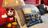 A decorative Mickey-themed throw pillow is positioned next to a Mickey bedside lamp.