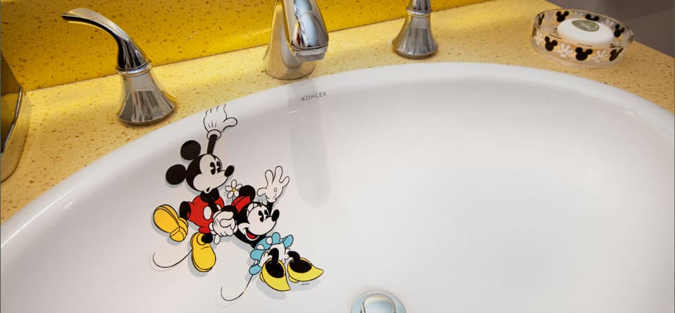 An image of Mickey has him holding the edge of the sink with one hand and, with the other, a dangling Minnie near the drain.