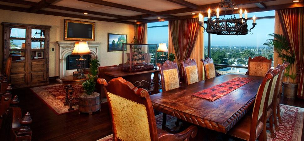 TV de pantalla plana sobre una chimenea decorativa en la sala de estar, y mesa de madera labrada en el comedor.