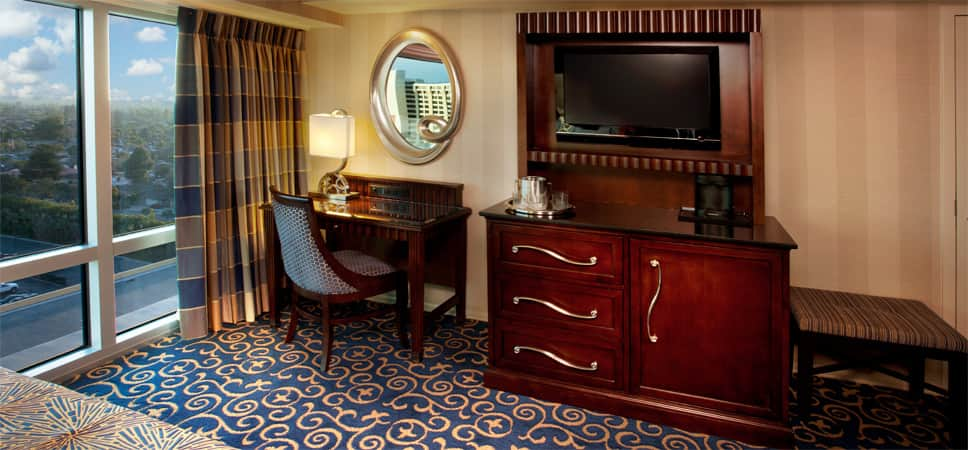 The room's furniture is designed in dark woods, and the carpeting is decorated with blue and gold curlicues.