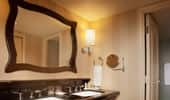 The elegant bathrooms have black granite counters and a large mirror framed by dark wood.