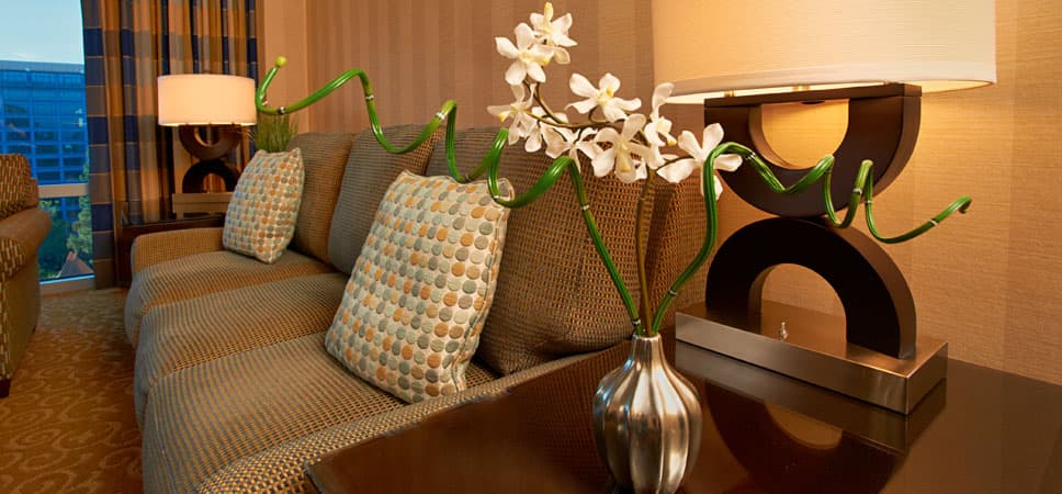 Beautiful room details: delicate flowers in a vase next to a lamp casting warm light