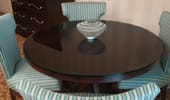 Dark wood round table surrounded by 4 dining chairs