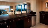A wet bar, dark wood cabinets and a view of Disneyland Resort from the living area of a 2-Bedroom Suite.