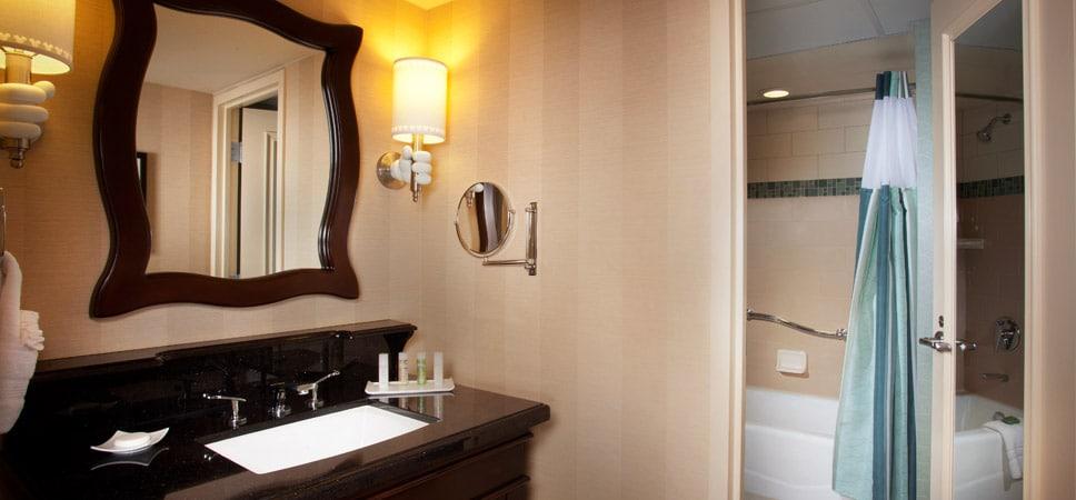 Los elegantes baños tienen lavabos de granito negro y un inmenso espejo de madera oscura