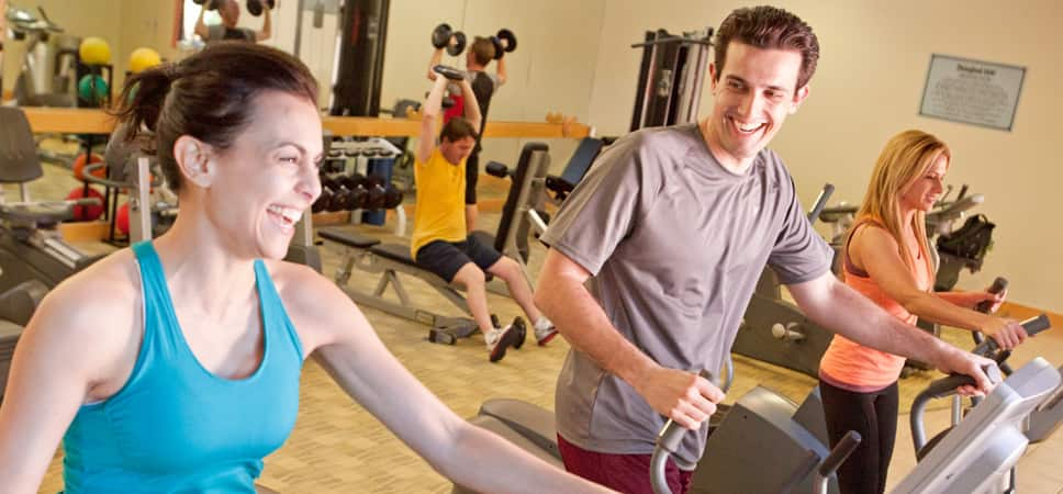 A man and woman work out on fitness equipment.
