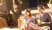 A pair of couples sit and enjoy drinks on the tiki-themed patio.