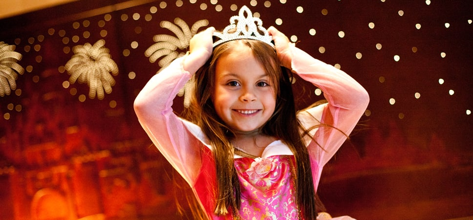While standing in front of the headboard, a young princess places a tiara on her head.