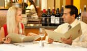 A couple, enjoying an evening out, discuss the delicious dinner selections on the menu.
