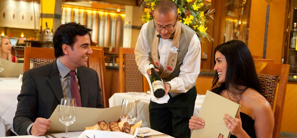 A sommelier recommends a wine to a couple dining at Napa Rose.