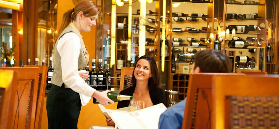 A server pours champagne for a seated couple.