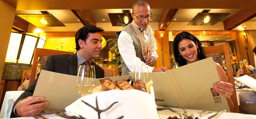 A couple seated at the table smiles while reviewing the menu and listening to the server answer their questions.