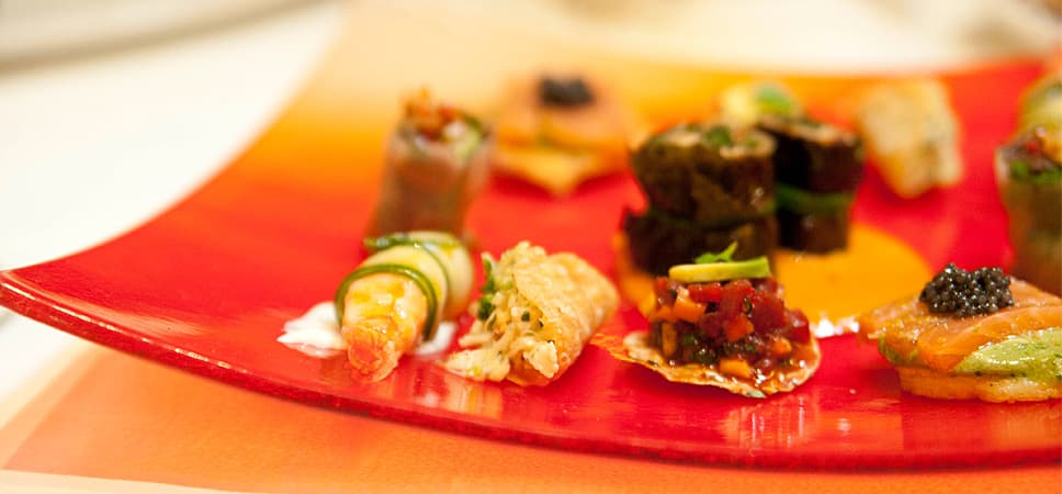A bright orange plate contains small tastes of sushi and exquisite appetizers.