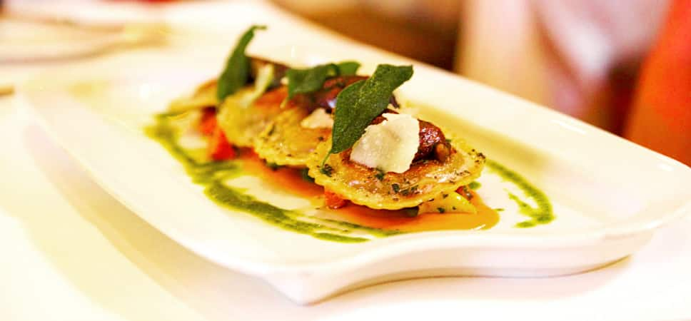 Beautifully plated stuffed ravioli pillows beneath buttered sage leaves.