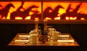A dinner table, set for Guests, sits near a wall that is decorated with silhouettes of cowboys and lit with a warm glow.