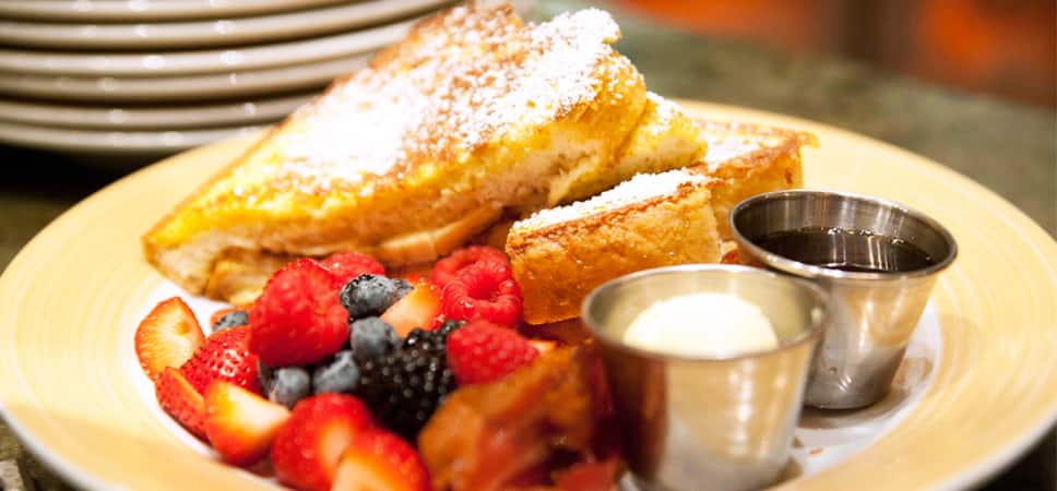 A plate of French toast and fruit.