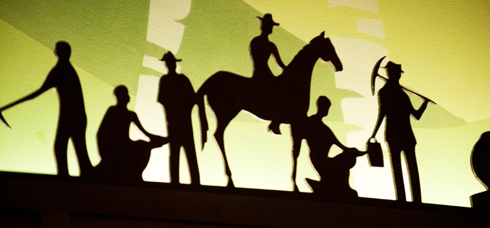 Close up on a sculpture that shows 6 figures in silhouette mining for gold.