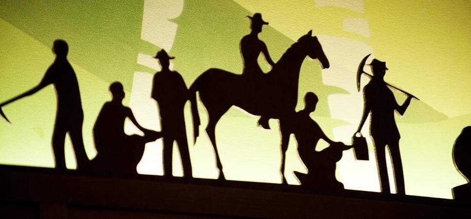 Acercamiento a una escultura que muestra 6 figuras en silueta
