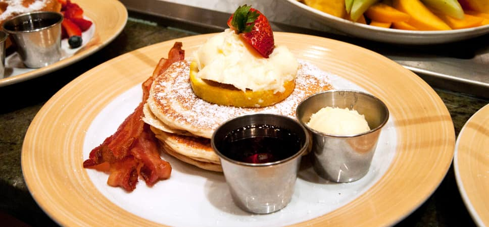 A plate piled high with pancakes and paired with bacon.