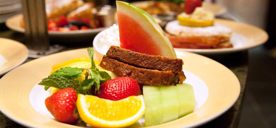 A plate of seasonal fruit and sweet bread.