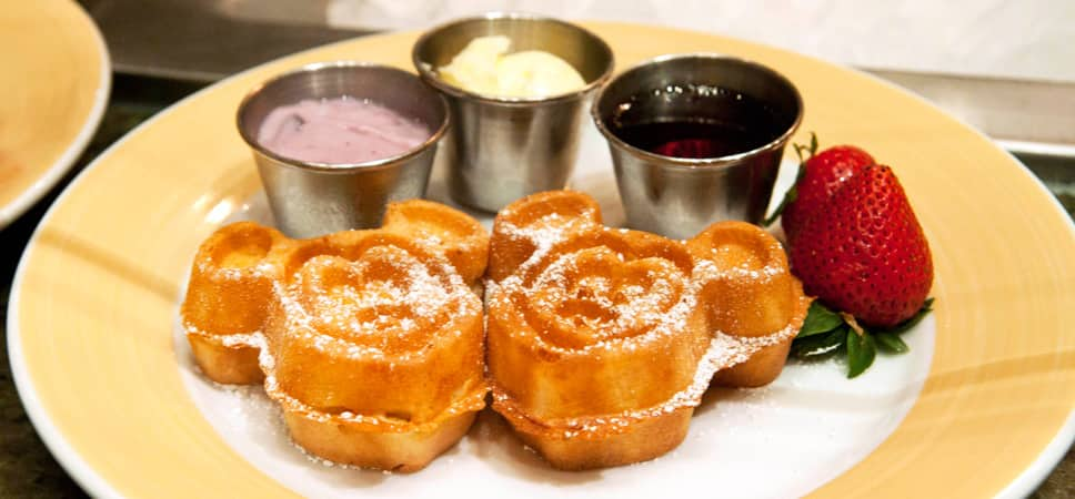 A plate with a pair of Mickey-shaped waffles sprinkled with powdered sugar, and 3 cups with topping options.