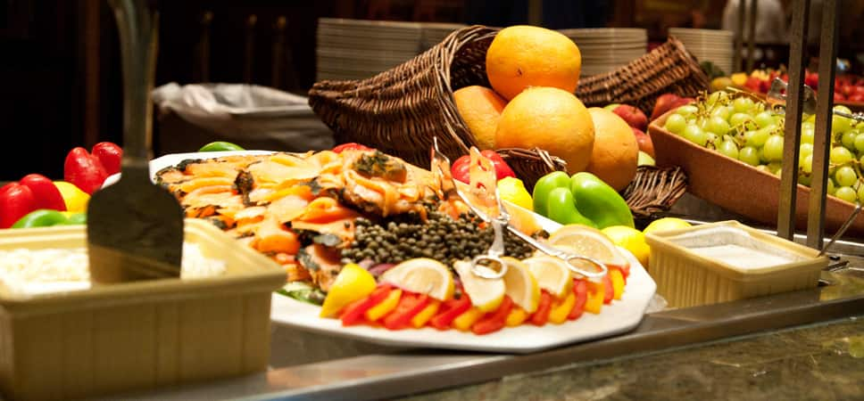 Buffet options include fresh fruits in a cornucopia basket and plates of lox, capers and lemons.