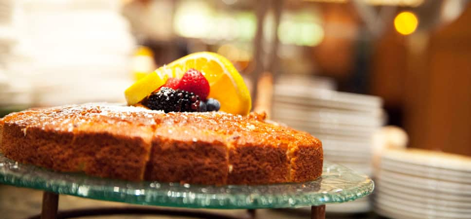 A sweet lemon cake is topped with fresh berries and a lemon slice.