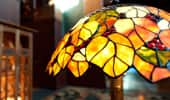 Close up on a hand-crafted glass lamp shade inspired by leaves glowing in golden California sunlight.